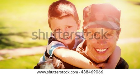 Portrait of happy soldier giving piggyback to his son in the park on a sunny day - stock photo
