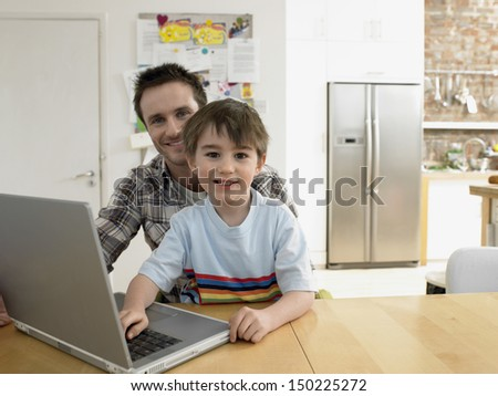 Portrait of happy son and father with laptop sitting at table in house - stock photo