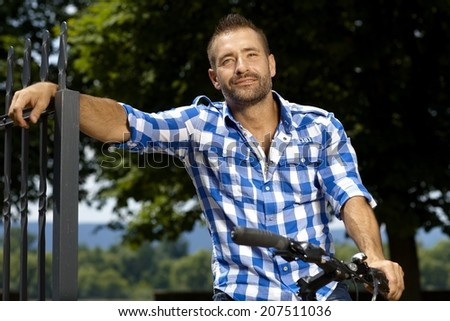 Portrait of happy, stubbly, caucasian, casual man on bicycle outdoor, leaning against fence. Smiling. - stock photo