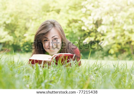 Portrait of happy student relaxed outdoors reading book.