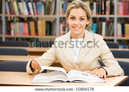 Portrait of happy student sitting in library before textbook and looking at camera - stock photo