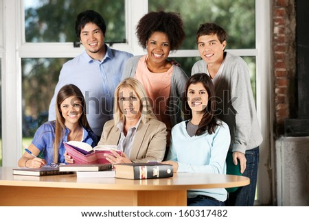 Portrait of happy students and teacher with books smiling at desk in classroom - stock photo