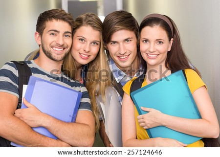 Portrait of happy students holding folders at college corridor - stock photo