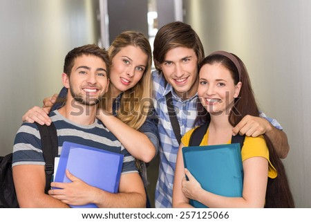 Portrait of happy students holding folders at college corridor