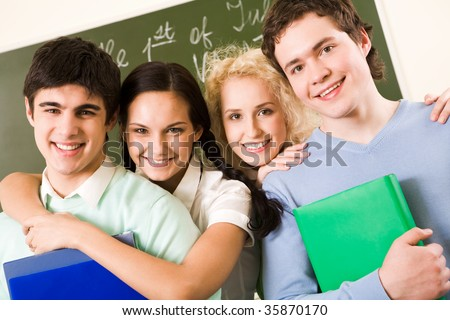 Portrait of happy students standing in line and looking at camera with smiles - stock photo