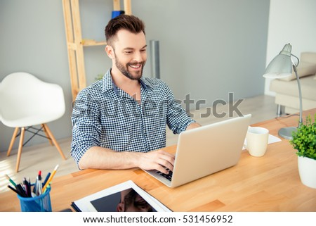 Portrait of happy successful businessman working in office on laptop.