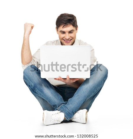 Portrait of  happy successful man working on laptop  in casuals - isolated on white. Concept communication.