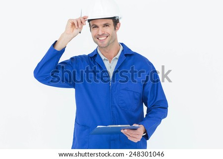 Portrait of happy supervisor wearing hard hat while holding clip board over white background - stock photo