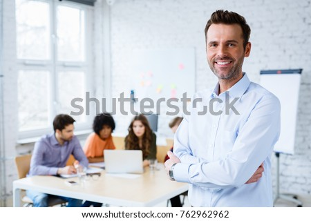 Portrait of happy teacher standing in classroom with students in background