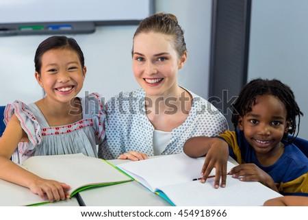 Portrait of happy teacher with schoolchildren in classroom - stock photo