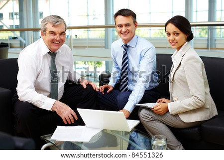 Portrait of happy team looking at camera at workplace