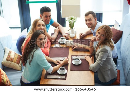 Portrait of happy teenage friends sitting in cafe and looking at camera - stock photo