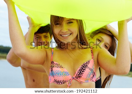 Portrait of happy teenage girl carrying mattress with her friends helping her - stock photo