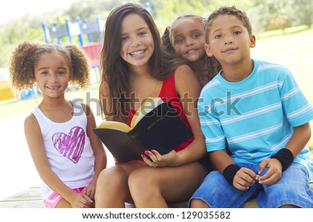 Portrait of happy teenage girl holding Holy Bible with siblings on park bench. Horizontal shot. - stock photo