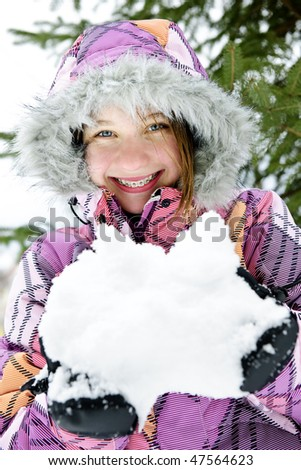 Portrait of happy teenage girl holding snow in gloves - stock photo