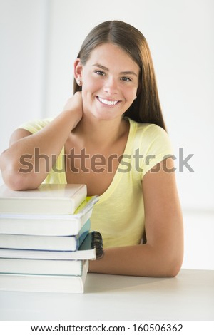 Portrait of happy teenage student leaning on stacked books in classroom