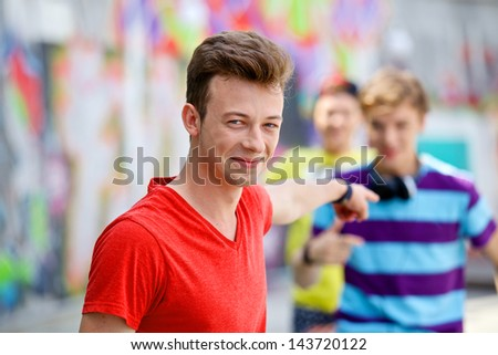 Portrait of happy teens boy with his friends by painted wall looking at camera