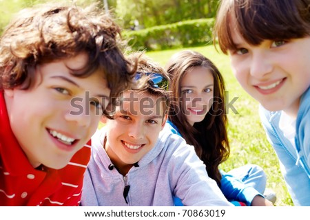 Portrait of happy teens looking at camera in the park at summer - stock photo