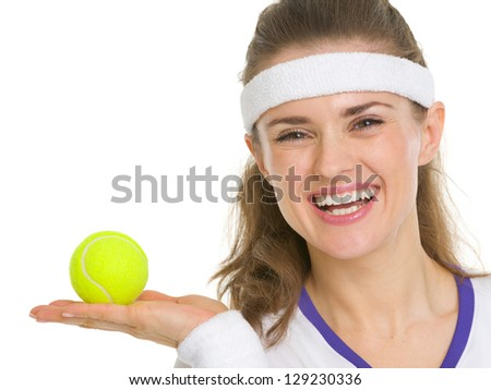 Portrait of happy tennis player showing tennis ball