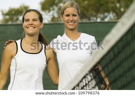 Portrait of happy tennis player standing arm around with her partner