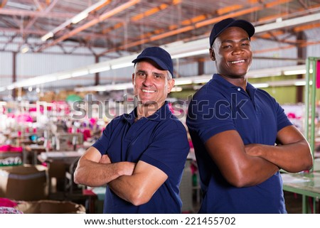 portrait of happy textile factory workers with arms crossed - stock photo