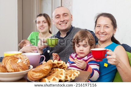 Portrait of  happy three generations family having tea and cakes  in home interior - stock photo