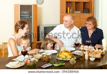 Portrait of happy three generations family posing together over celebratory table at home interior - stock photo