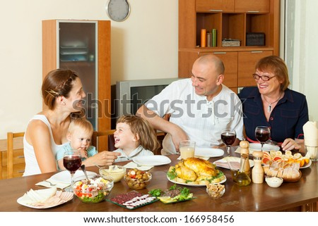 Portrait of happy three generations family together around festive table at home