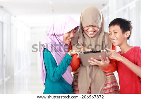 portrait of happy three kids playing tablet computer in school