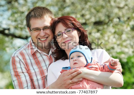 Portrait of happy three person smiling family standing outdoors over spring bloom - stock photo