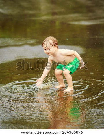 Portrait of happy toddler boy playing with water in puddles during rain thunderstorm on bright summer day outside, recreation leisure concept, childhood freedom, motion blur and freeze motion effect - stock photo