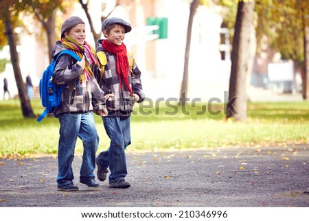 Portrait of happy twin schoolboys going to school - stock photo