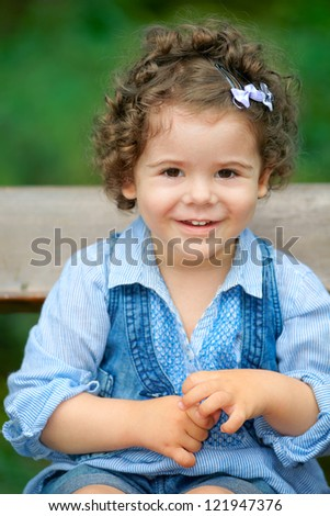 Portrait of happy two year old little girl outdoor sitting on a bench.