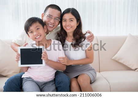 Portrait of happy Vietnamese family sitting on the sofa with a digital tablet - stock photo
