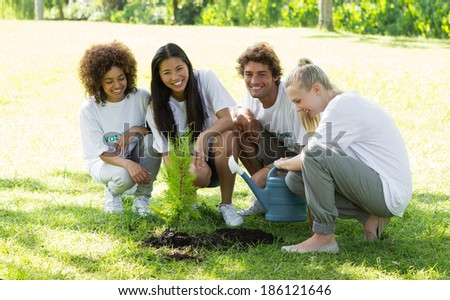 Portrait of happy volunteers planting in park