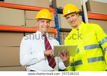 Portrait Of Happy Warehouse Worker And Manager In A Warehouse - stock photo