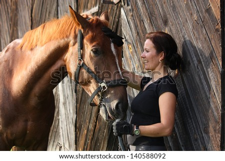 Portrait of happy woman and brown horse near the barn - stock photo