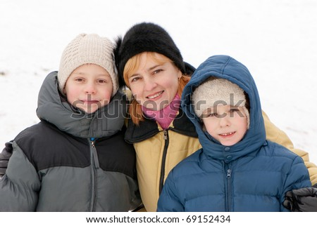 Portrait of happy woman and cheerful boys in winter