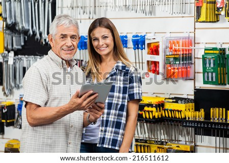 Portrait of happy woman and father with digital tablet in hardware store