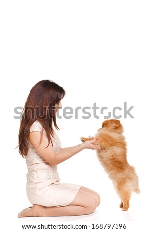 Portrait of Happy woman and her beautiful little red dog spitz over white background