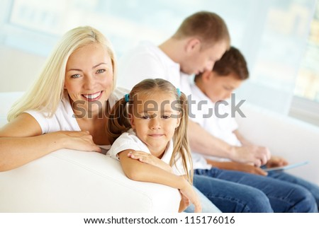 Portrait of happy woman and her daughter on background of father and son