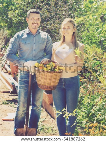 Portrait of happy woman and man greenhouse workers with flower basket. Focus on man