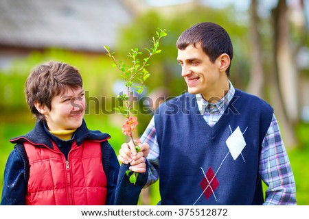 portrait of happy woman and man with disability together on spring lawn - stock photo