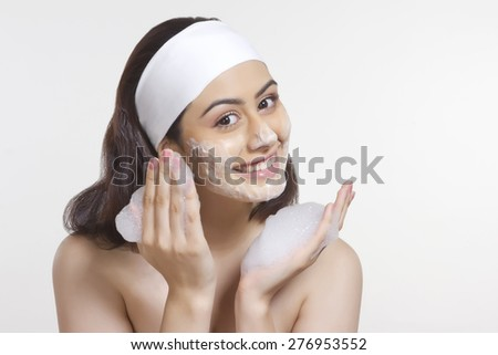 Portrait of happy woman applying soap sud on face against white background