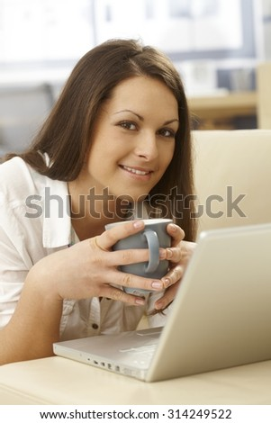 Portrait of happy woman at home drinking tea, using laptop, smiling, looking at camera.