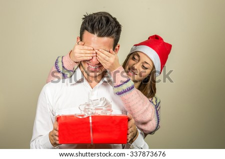 Portrait of happy woman closing male's eyes by her hands while he holding giftbox