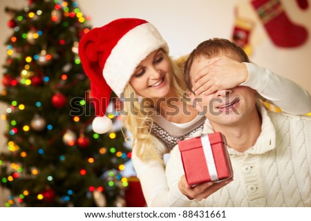 Portrait of happy woman closing male?s eyes by her hands while holding giftbox in front of him - stock photo