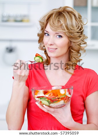 Portrait of happy woman eating the salad of vegetables in the kitchen - stock photo