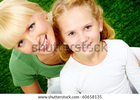 Portrait of happy woman embracing her pretty daughter and both looking at camera - stock photo