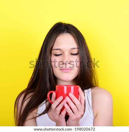 Portrait of happy woman enjoying cup of hot drink against yellow background - stock photo